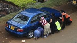 Kenyans take cover behind car