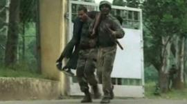 Injured man being carried from army base