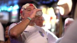 Man in an England shirt drinking beer