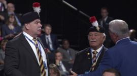 Retired army colonel and friend being addressed by usher