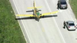 The plane taxis past cars on the road