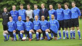 The Duke of Cambridge stands with members of the Polytechnic FC prior to their match against the Civil Service FC, in the grounds of Buckingham Palace
