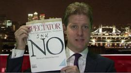 Fraser Nelson holds up the latest issue of the Spectator