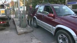 A man in a rural community filling his car with fuel