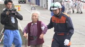 Elderly woman is helped to a boat