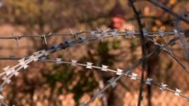 Man stands behind razor wire
