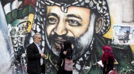 People walk past Arafat mural in Gaza City