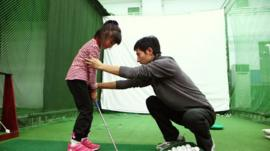 A coach adjusts a child's stance