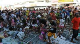 Residents watch as others throw looted goods from a warehouse in the town of Guiuan, Eastern Samar province in the central Philippines