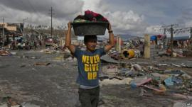 A man carrying goods through the disaster zone at Tacloban, in the Philippines