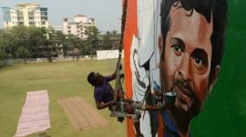 An Indian artist works on a mural of cricketer Sachin Tendulkar on the wall of a sports club building in Mumbai