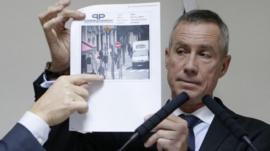 Francois Molins holds an image of the suspect