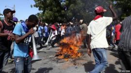 Protesters circle a burning road block