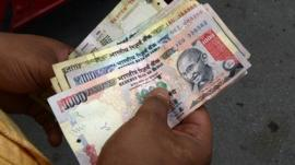 A man counts Indian rupee notes