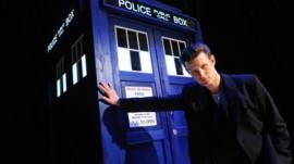 Matt Smith stands next to Tardis