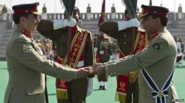 Pakistan's outgoing army chief General Ashfaq Kayani (R) hands over the baton of command over to the newly appointed army chief General Raheel Sharif