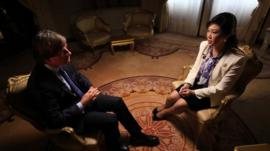 Thailand's Prime Minister Yingluck Shinawatra (R) speaks to the BBC's Jonathan Head
