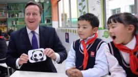 UK Prime Minister David Cameron holding a picture of a panda, with Chinese school children