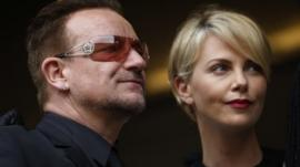 Actress Charlize Theron waits with musician Bono for the memorial service for former South African president Nelson Mandela at the FNB Stadium