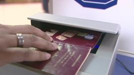 Traveller holding passport in scanner