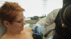 Woman having her nipple tattooed