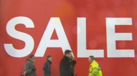 People walk past a sale sign
