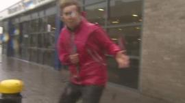 BBC reporter Sarah Ransome struggles to stay upright in high winds outside Plymouth station