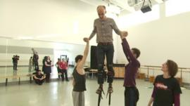 Colin Paterson being taught how to use stilts by Northern Ballet's circus skills team