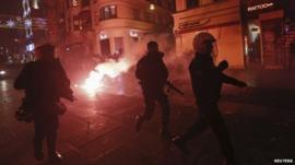 Turkish riot police chase demonstrators during an anti-government protest in Istanbul