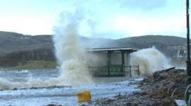 A shelter in Deganwy, Conwy, is battered by waves