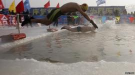 Swimmers dive into ice covered Songhua River, Harbin