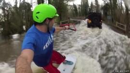 Man wakeboards down flooded road