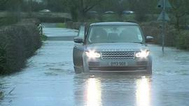 A car drives through flood water
