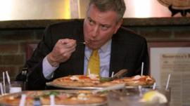 New York Mayor Bill de Blasio eating a pizza