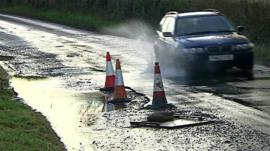 Car going through pothole