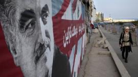 A Lebanese woman passes a portrait of slain Lebanese Prime Minister Rafik Hariri