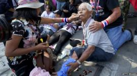 A man injured by an explosion is helped after an explosive device went off during an anti-government protest march in Bangkok on 17 January 2014