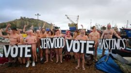 Nude people on a beach with a sign that reads