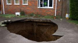 Phil Conran looks out of a window from his home at the sinkhole
