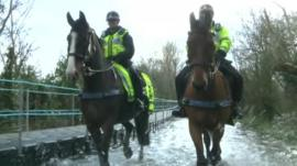 Police officers on horses in flood water