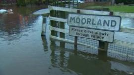 Village sign in flooded village of Moorland, Somerset