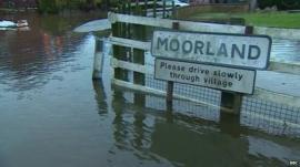 Village sign in flooded village of Moorland, Somerset