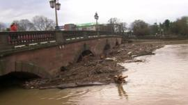 Debris and silt gathered around bridge supports in Worcester
