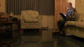 Man sits on sofa in flooded room
