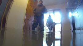 Men stand in flood water inside house