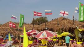 Tourists on an Indian beach with international flags