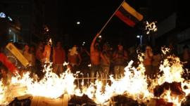 Opposition demonstrators hold a Venezuelan flag in front of a burning barricade in Caracas