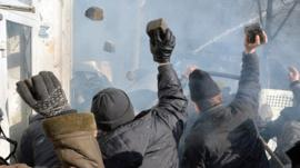 Anti-government protesters throw rocks during clashes with police in Kiev