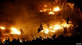 Anti-government protesters stand behind burning barricades in Kiev's Independence Square on 19 February 2014.