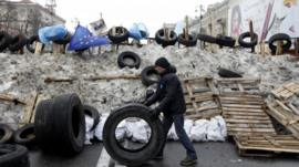 A man rolls a tyre at a barricade erected by Pro-European integration protestors in central Kiev